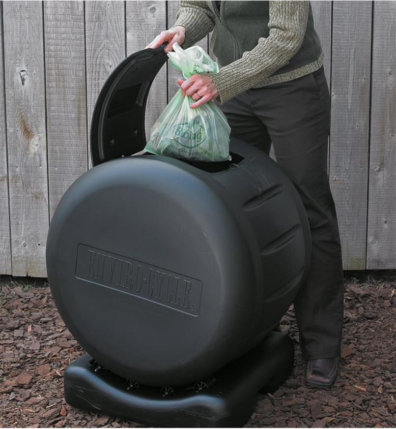 A woman places a full compostable bag inside a rolling compost bin