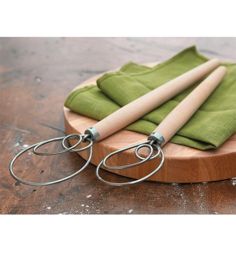 Both sizes of Danish Dough Whisks lying across a cutting board