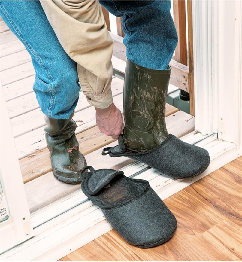Man putting on first boot slipper over muddy boot before coming inside