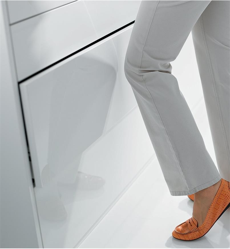 A woman closes a drawer by pushing it with her knee
