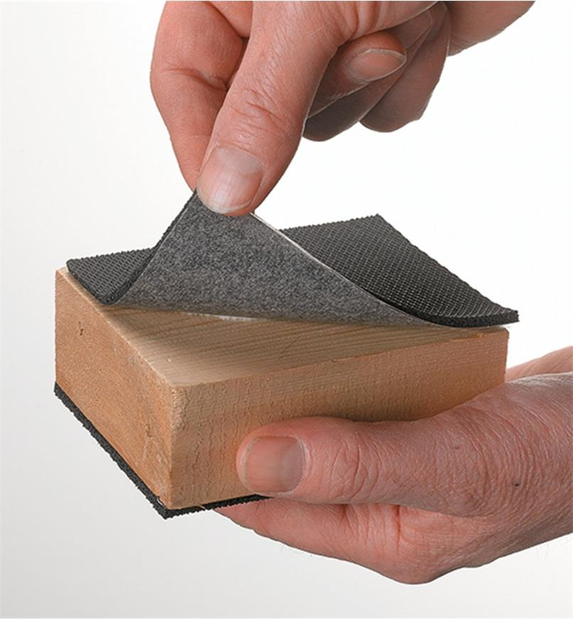 Squares of high-friction sheet material adhered to either side of a block of wood