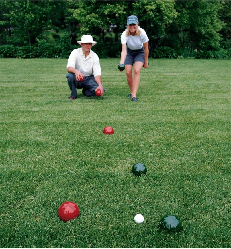 A woman throws a bocce ball toward the target ball while a man waits for his turn