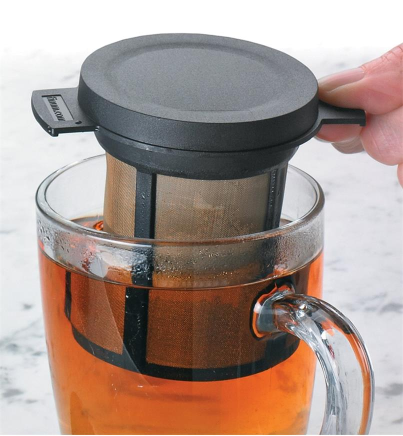 Brew Basket being lifted out of a glass mug of tea