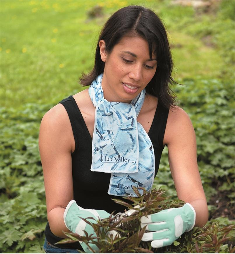 A woman wears a Cooling Towel while pruning in the garden