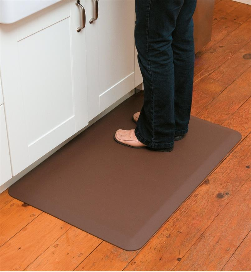 "A person standing on a 24"" x 36"" brown Stationary Mat by a counter"