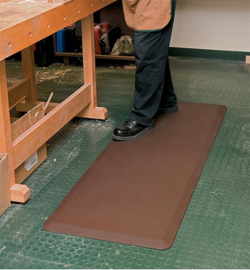 "A person stands on a 24"" x 72"" brown Stationary Mat beside a workbench"