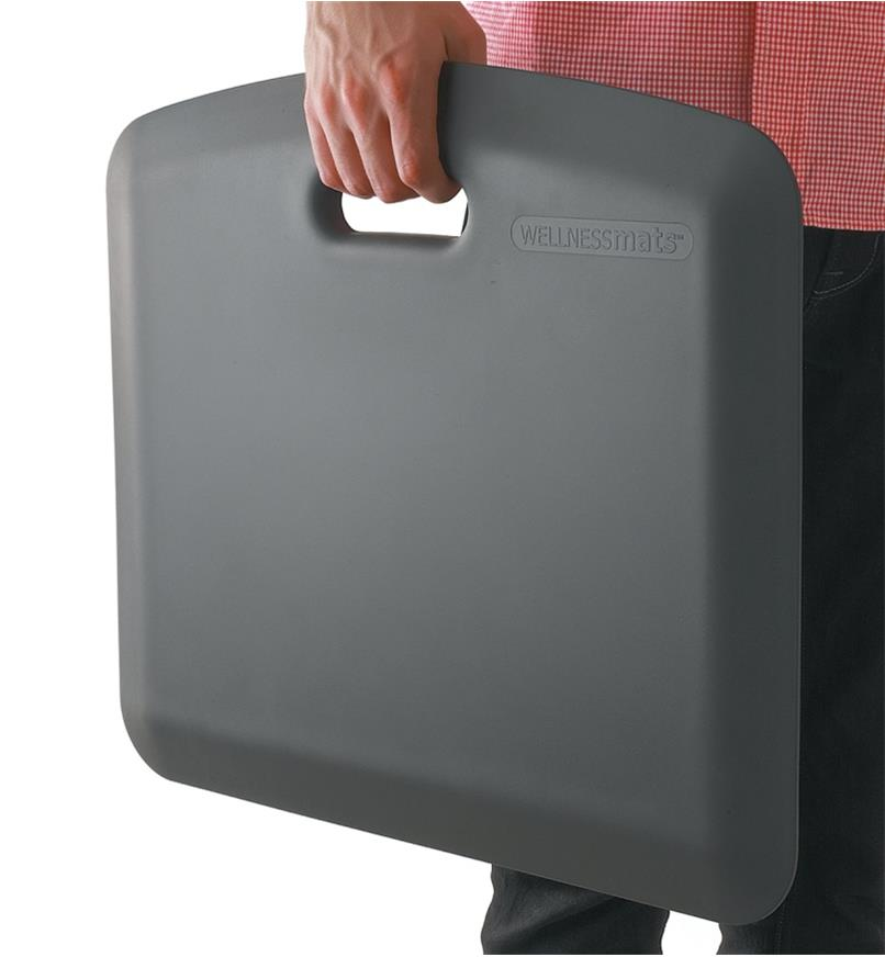 "Carrying an 18"" x 22"" gray Portable Mat by the molded handle"
