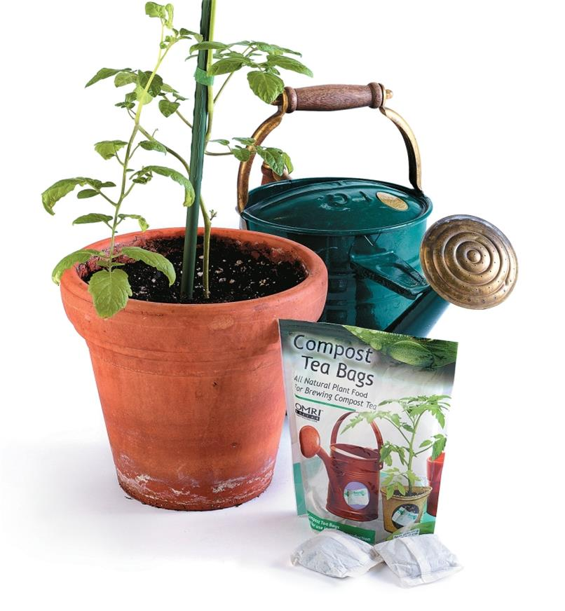 Package of Compost Tea Bags next to a potted plant and a watering can
