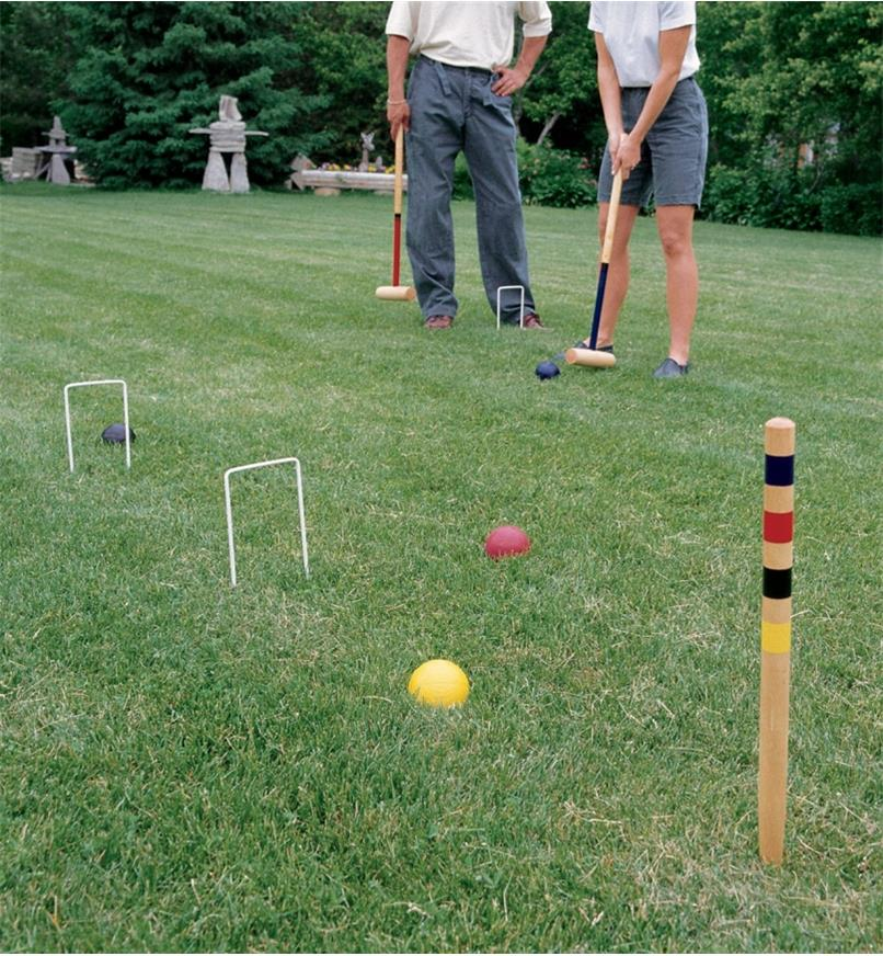 A man and woman playing croquet on grass