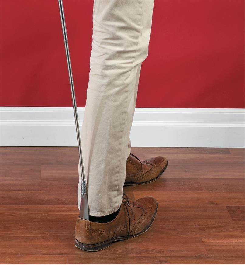 A person puts on a shoe with the help of the Extendable Shoehorn