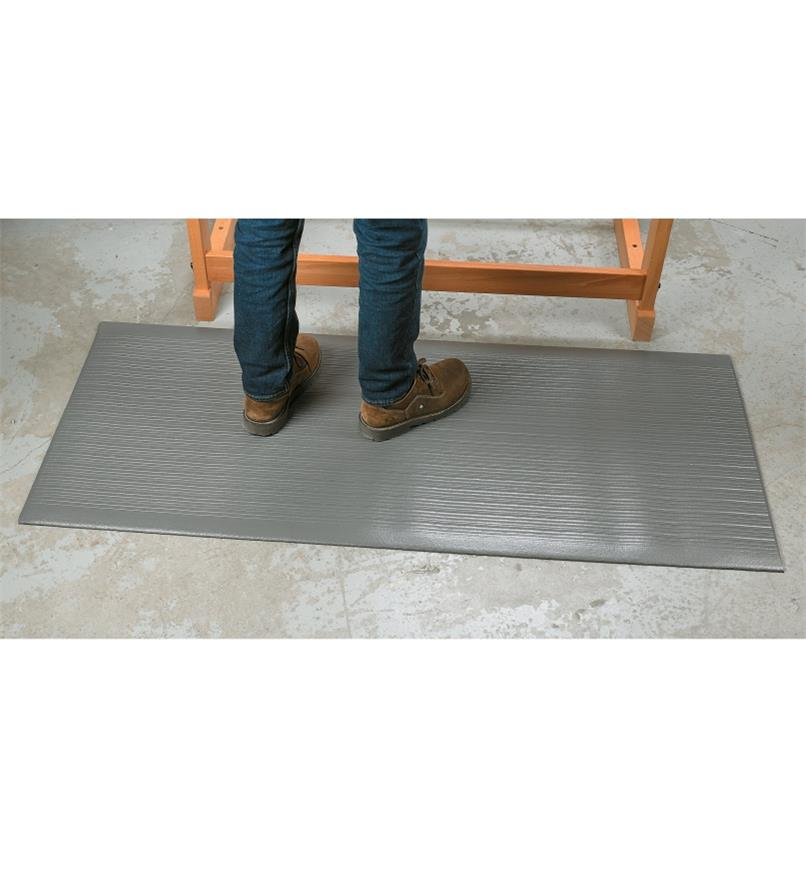 A person standing on a Foam-Cell Anti-Fatigue Bench Mat beside a workbench
