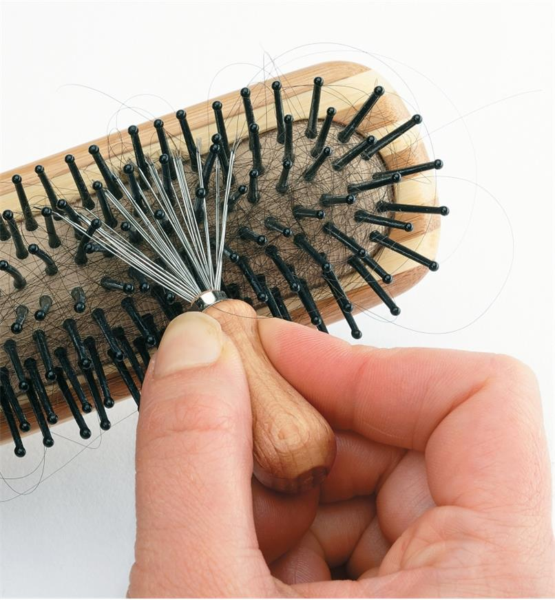 Using the hairbrush-cleaning brush to clean between the bristles of a brush