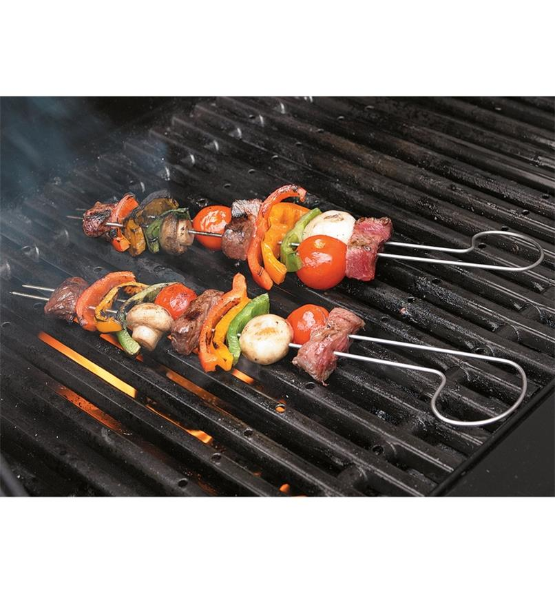 Meat and vegetables on two double-prong skewers being grilled on a barbecue