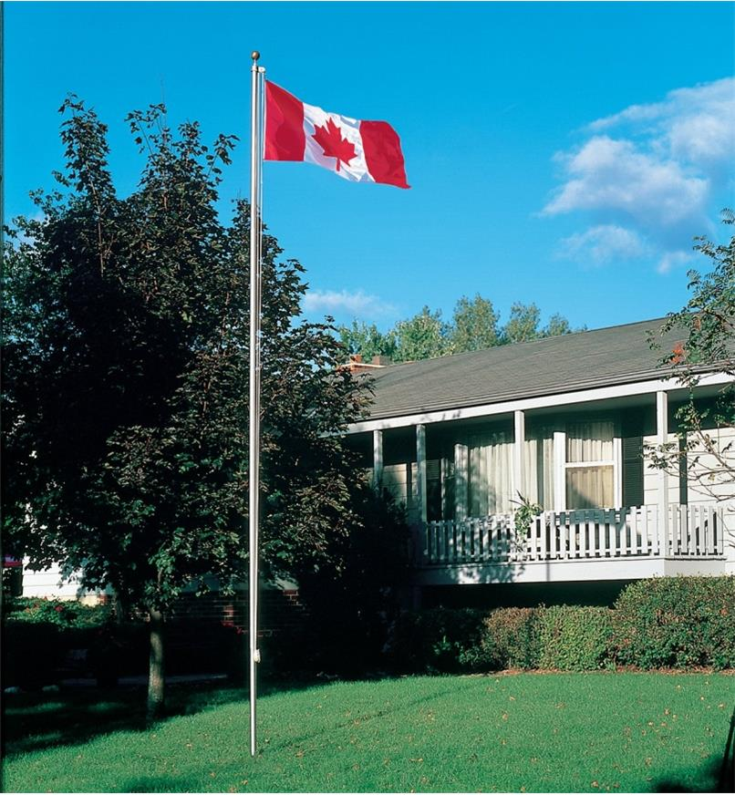 Deluxe Canadian Flag raised on a flagpole in front of a house