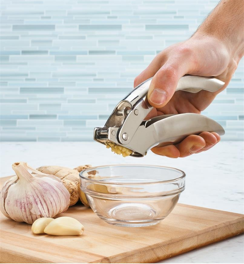 Using the garlic press to mince garlic into a bowl