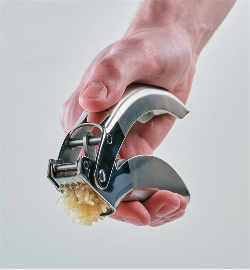 Pressing the handles on the Garlic Press to mince garlic