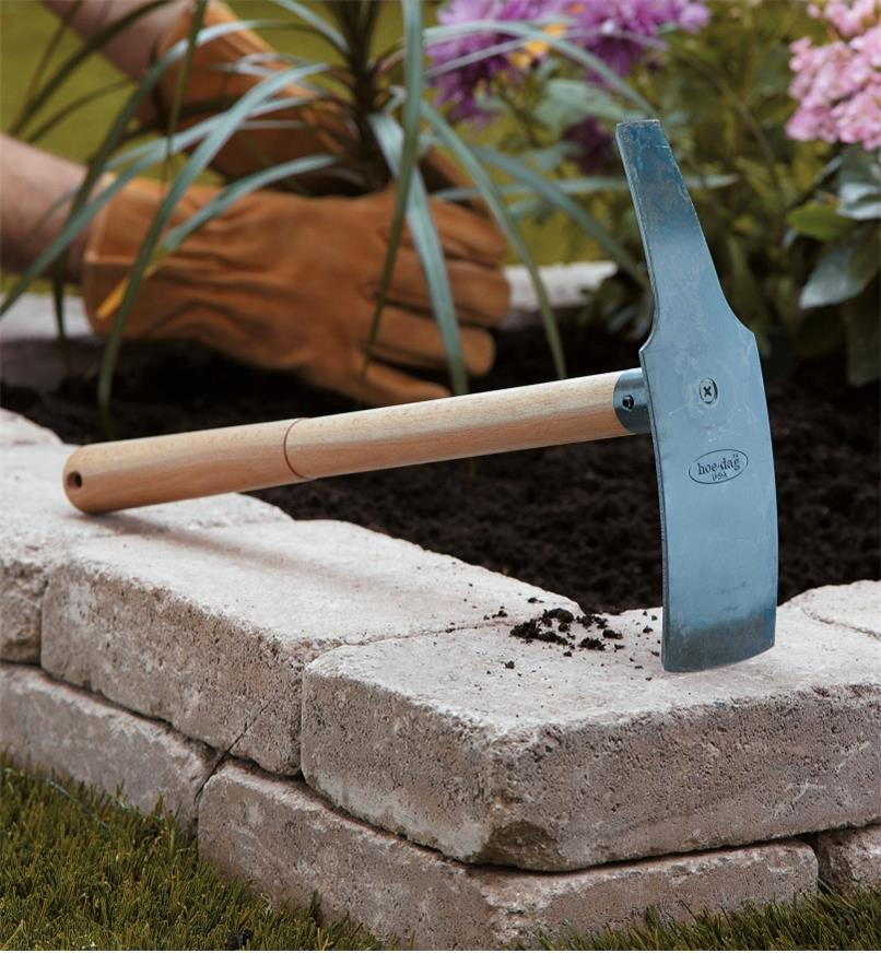 Hoe Dag resting on stone garden edging