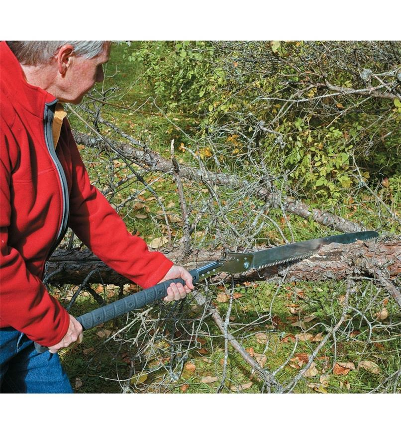 A man cuts into a fallen tree using the Folding Trail Saw