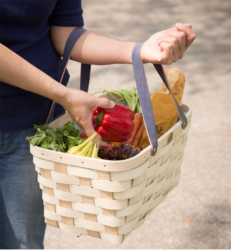 A woman holds a Handwoven Basket Tote filled with produce and a baguette