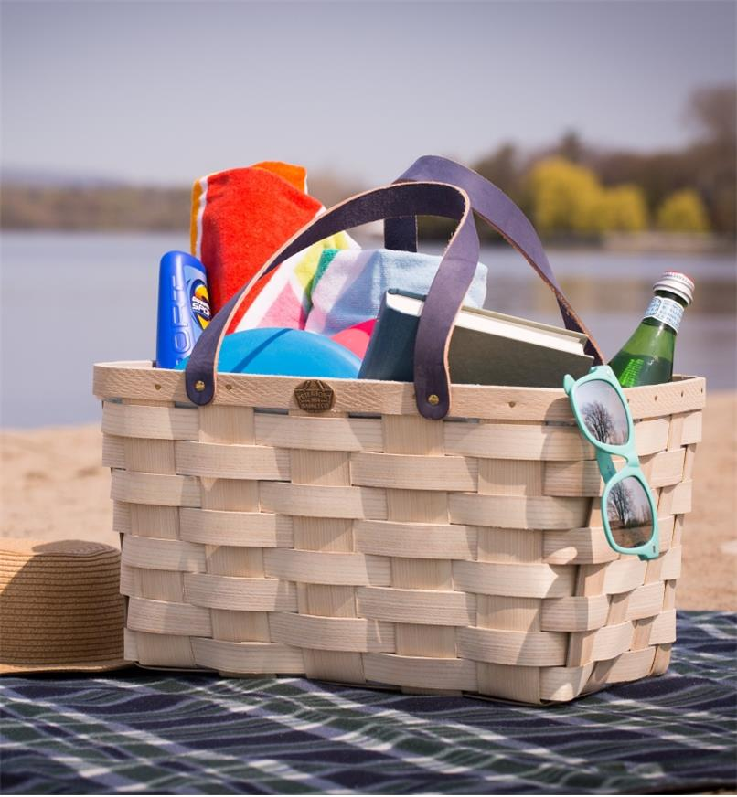 Handwoven Basket Tote on a blanket on a beach, holding towels and other beach accessories