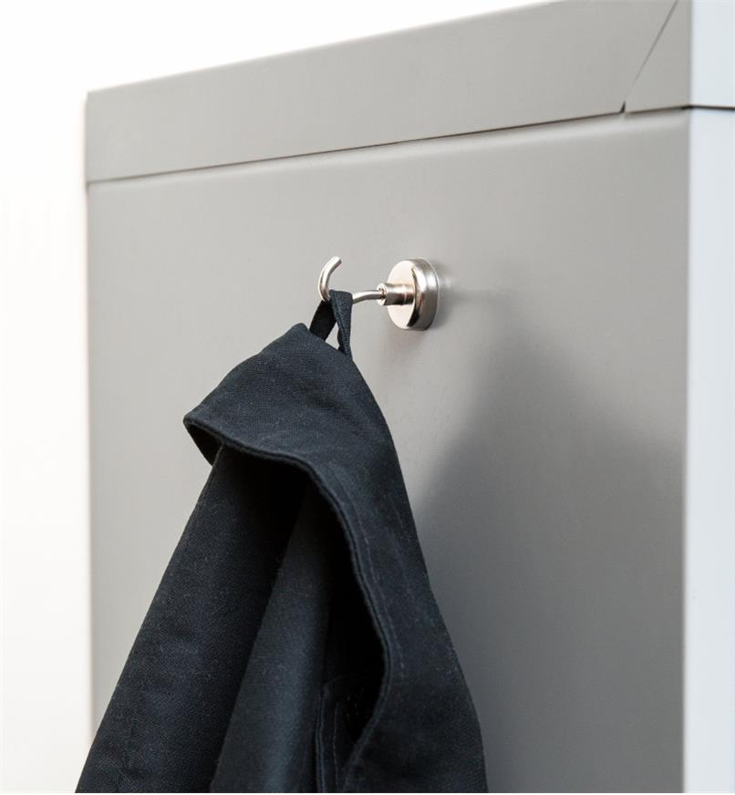A jacket hanging on a magnet-mounted hook attached to a metal cabinet