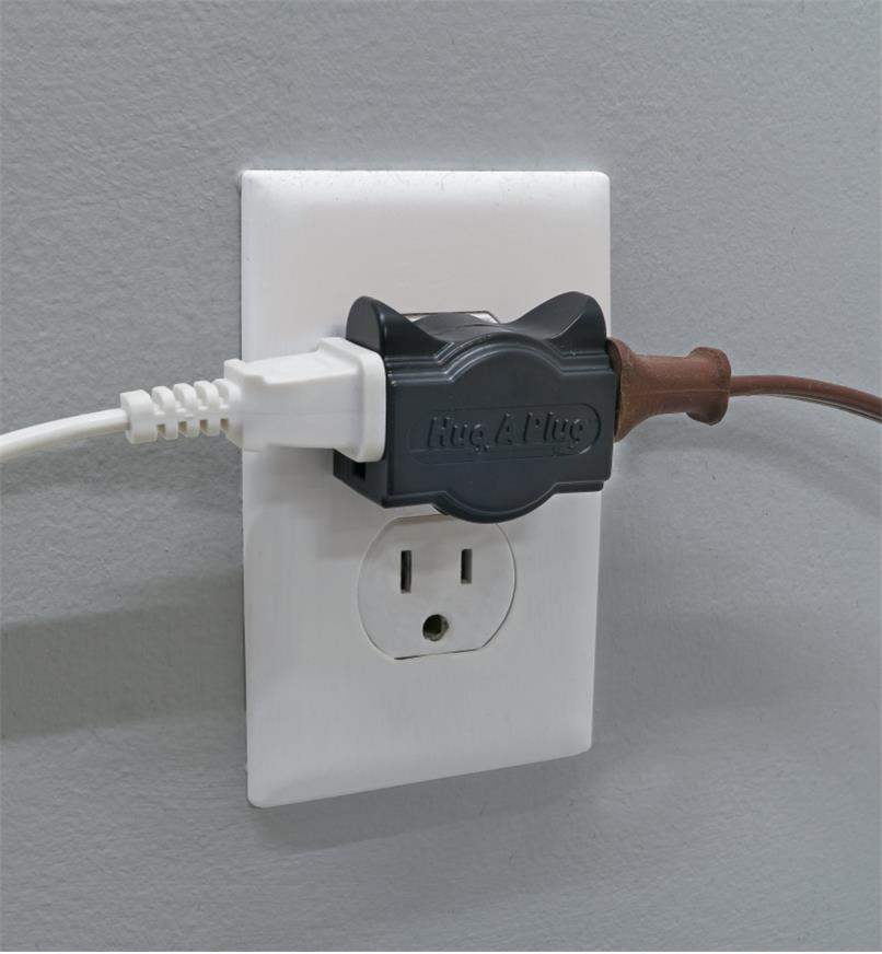 Black Hug-A-Plug adapter, with two plugs attached, plugged into a wall outlet