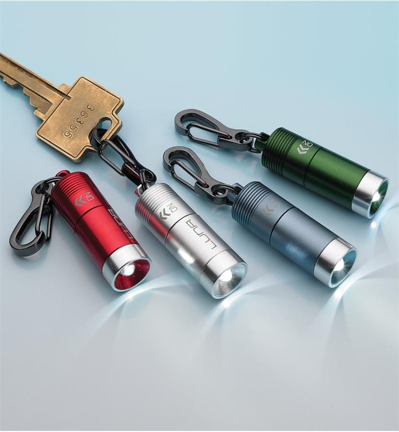 Four mini clip LED lights in different colors, with one attached to a key