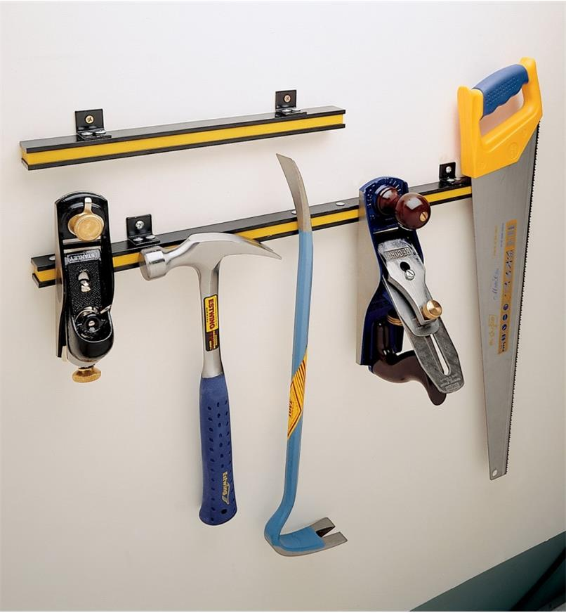 "Both sizes of tool bar attached to a wall, with various hand tools clinging to the 24"" size"