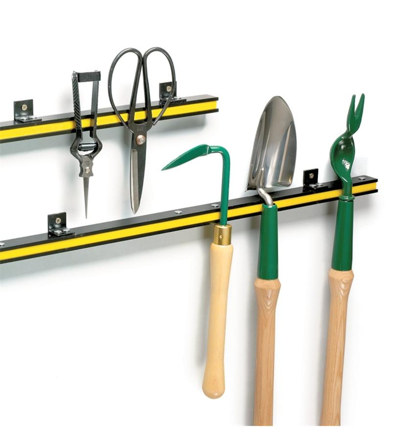 Both sizes of tool bar attached to a wall, with various garden tools clinging to them