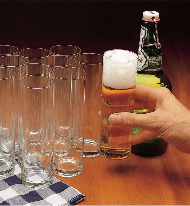 Set of 12 Kolsch glasses, one filled with beer, being lifted in a hand, next to a beer bottle