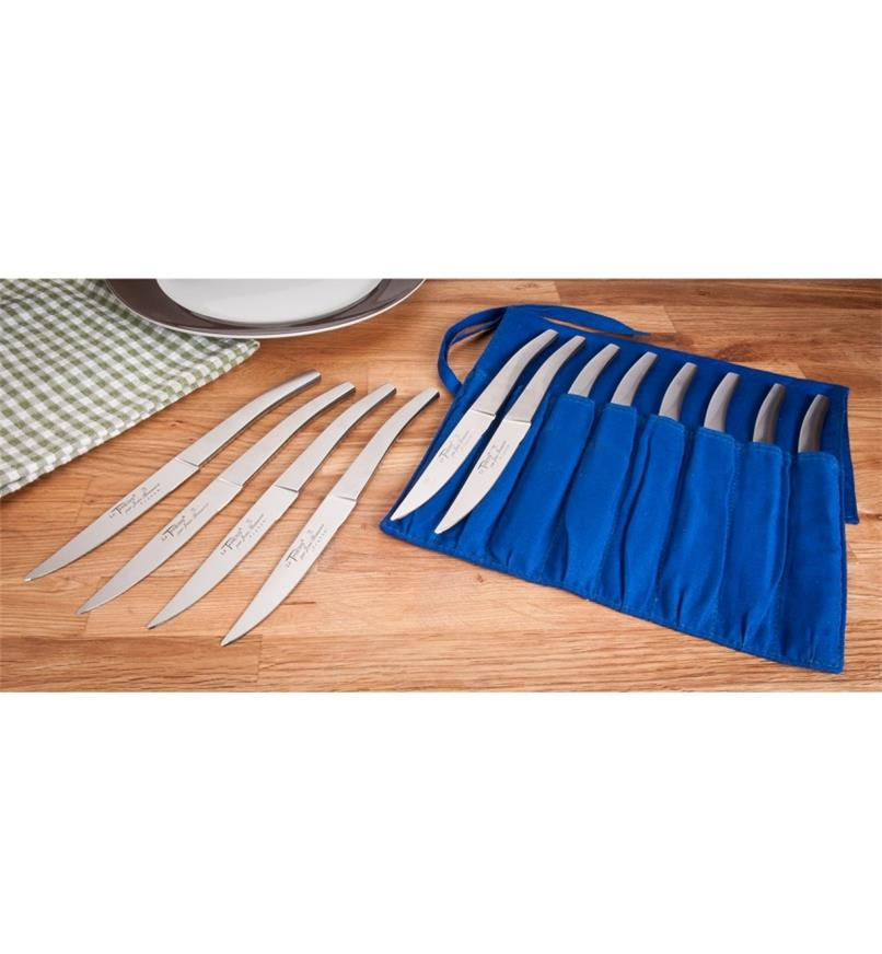 Set of eight bistro knives in roll beside set of four on dining table