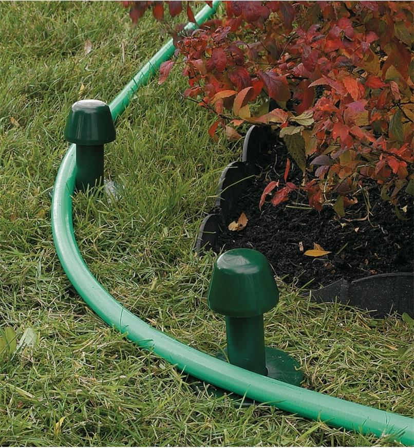 A hose looped around two hose guides beside a garden bed