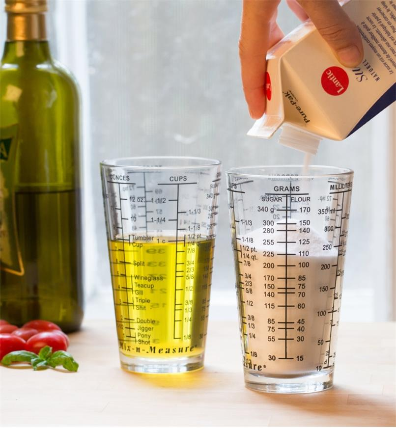 Two measuring glasses, one holding sugar and the other oil