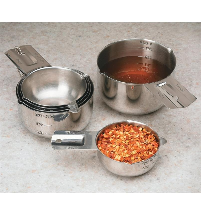 Set of 6 Lifetime Measuring Cups, one filled with pepper flakes and another with wine vinegar