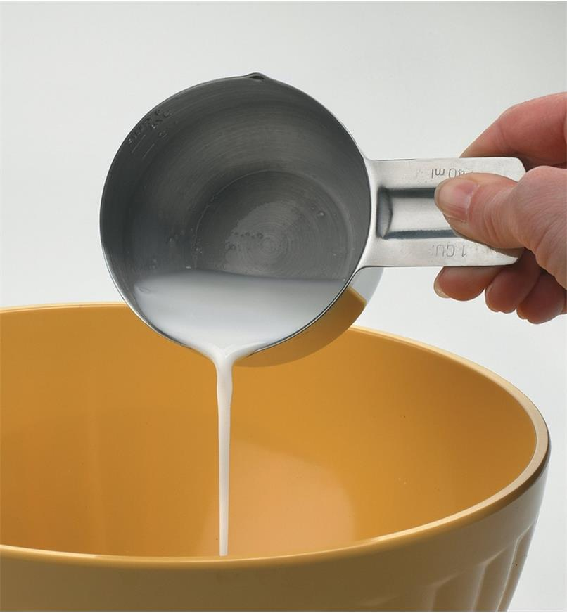 Pouring milk from a measuring cup into a mixing bowl