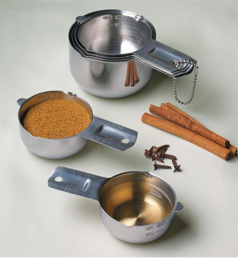 Set of 6 Lifetime Measuring Cups, one filled with ground cinnamon and another with oil