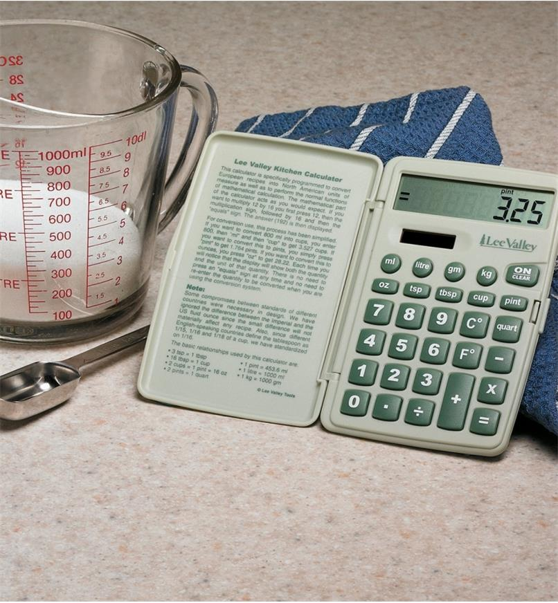 Lee Valley Kitchen Calculator propped on a counter next to a measuring cup and spoon