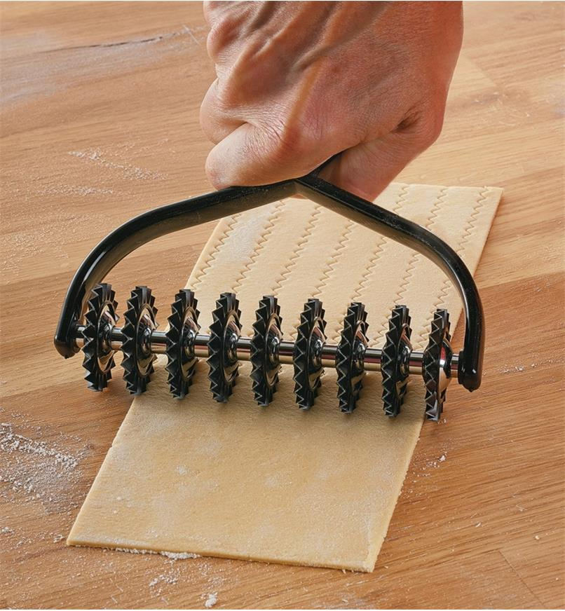 Rolling the Marcato Pasta Cutter over a sheet of pasta to cut it into strands