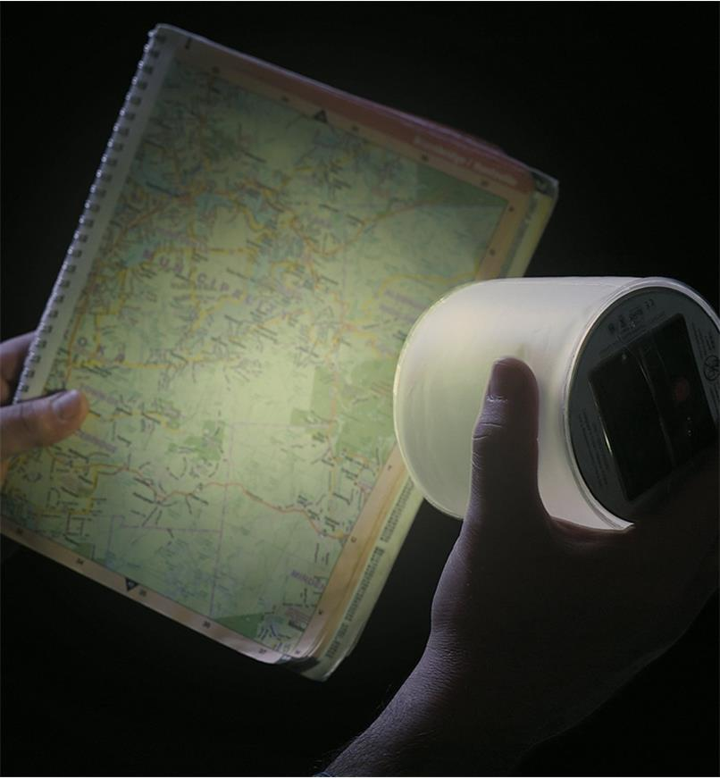 Using the Emergency Luci Lantern to illuminate a map in the dark