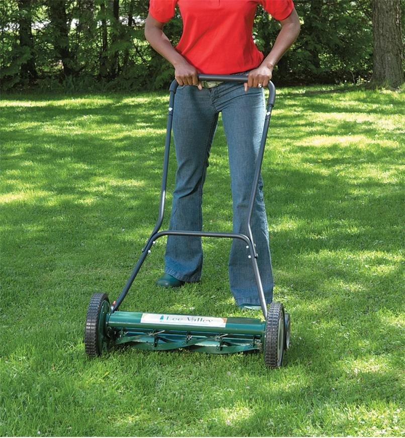 "A woman pushes the Lee Valley 20""  Mower over grass"