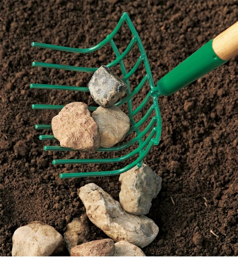 Scooping rocks from soil into the rock rake's basket-like head