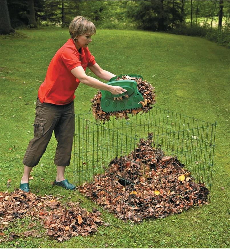 A woman uses Leaf Paws to transfer leaves to a compost bin
