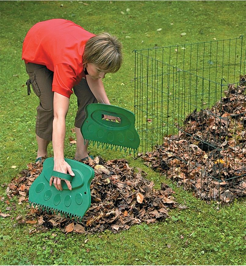A woman uses Leaf Paws to pick up a pile of leaves on a lawn
