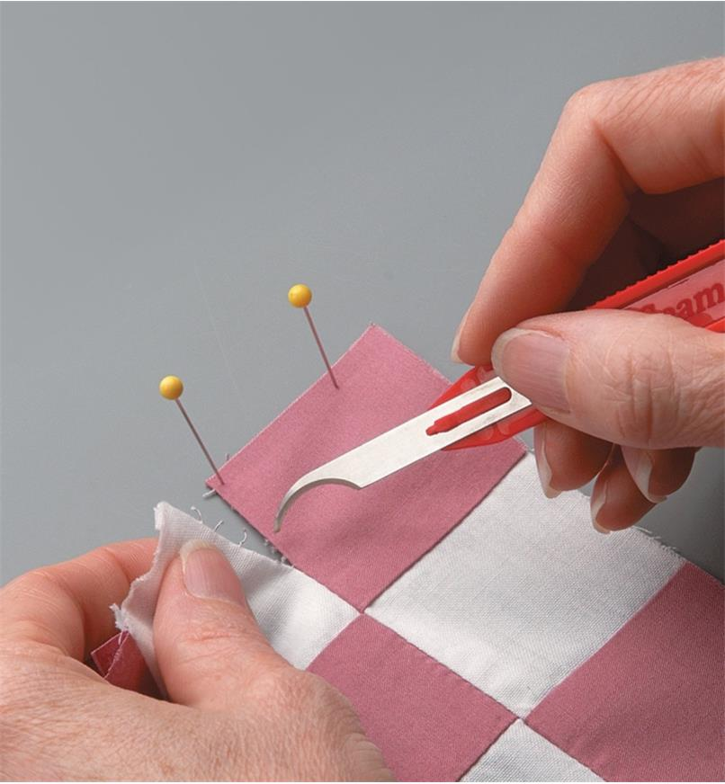 Using the seam-ripper tool to continue opening a seam that has been started with the stitch-picker