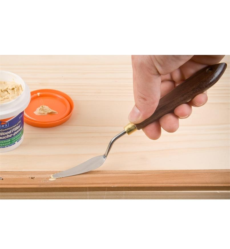 Using a palette knife to apply wood filler