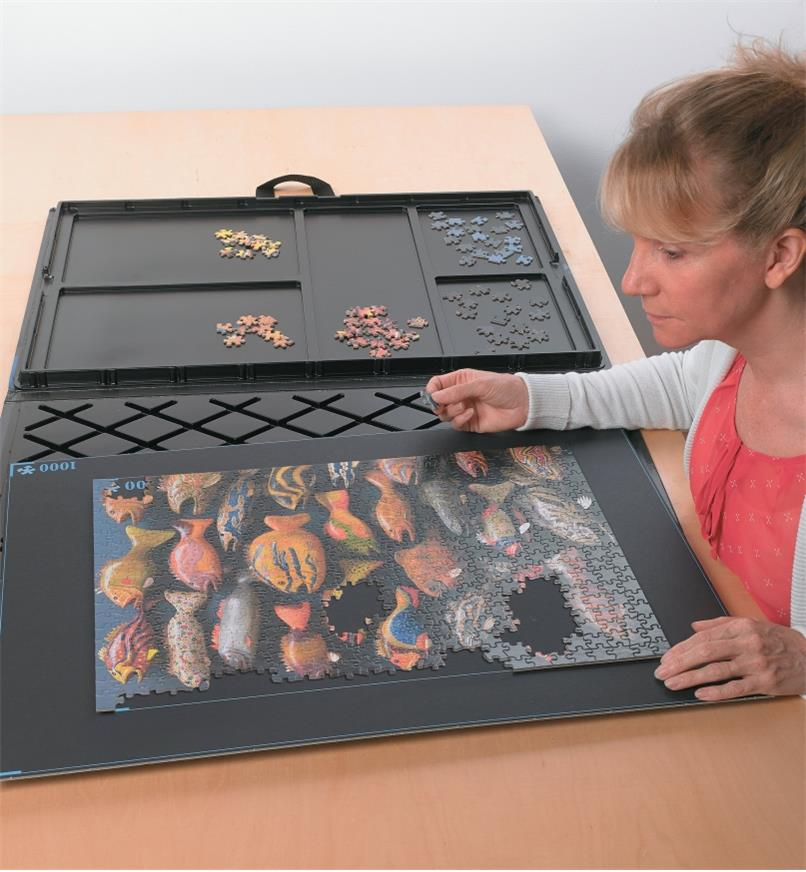 A woman assembles a puzzle on the assembly board of the puzzle caddy