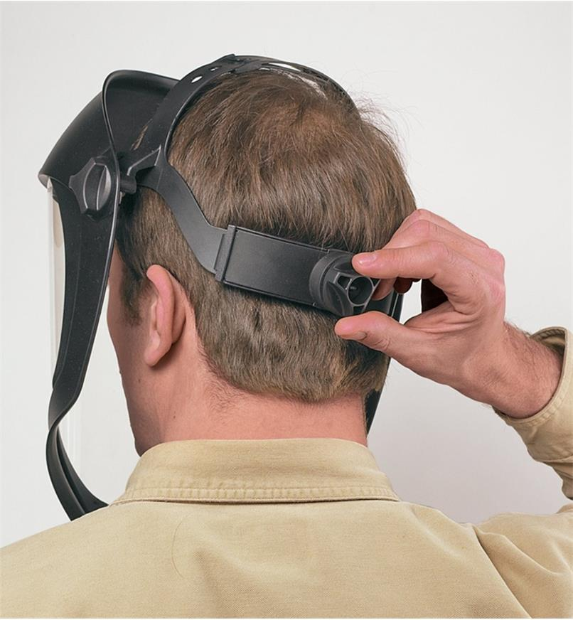 Back view of a man wearing the Professional Face Shield, adjusting it using the rear knob