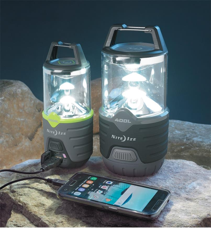 Both Nite Ize Radiant Lanterns sitting on a rock, with the rechargeable model charging a smartphone