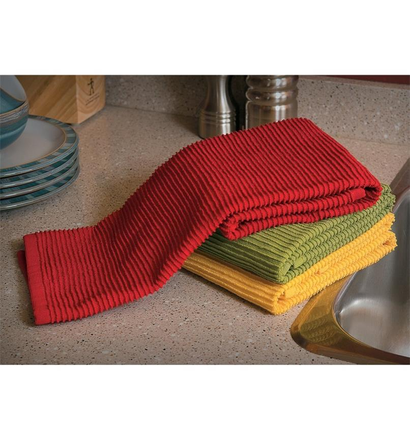 Set of 3 Ripple Towels (yellow, red, green) folded and piled on a kitchen counter