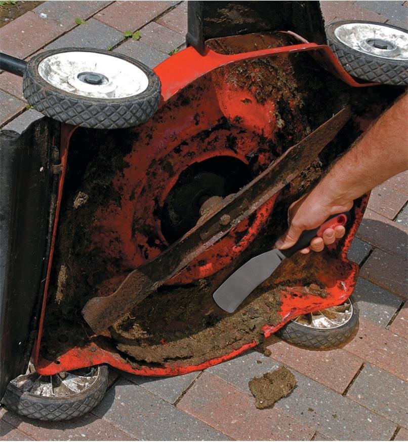 Grattoir pour tondeuse Grassbuster employé pour déloger les débris collés au carter d'une tondeuse